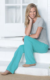 Model sitting on step outside wearing PajamaJeans - Bootcut Aqua paired with tan flats and a Gray t-shirt image number 2