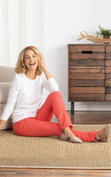 Model sitting on the ground wearing Coral Skinny PajamaJeans paired with a white long sleeve shirt and tan flats. image number 3