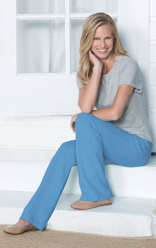 Model sitting wearing Cool Blue Bootcut PajamaJeans paired with a gray t-shirt and flats. image number 3