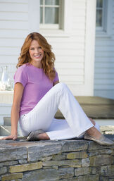 Model sitting outside wearing White Bootcut PajamaJeans paired with gold flats and a Lavender t-shirt image number 2